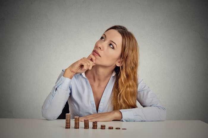 Woman sitting down with stacks of pennies in front of her