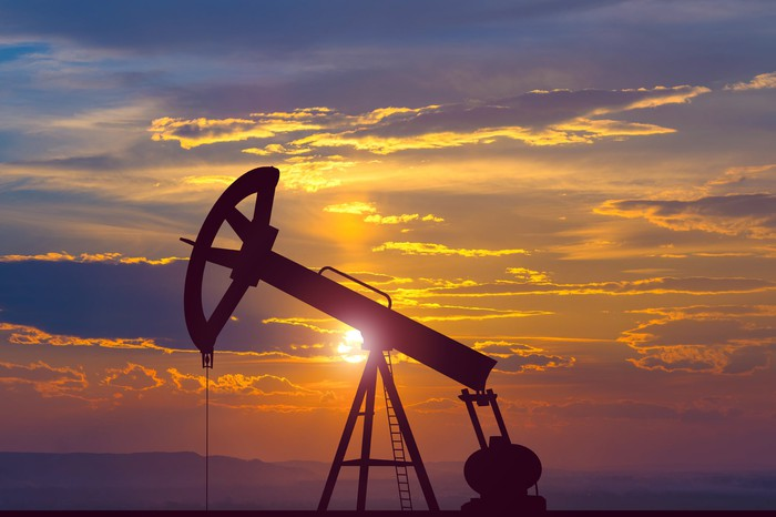 An oil pumpjack with a sunset backdrop.