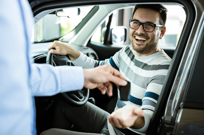 A man sitting in a car receives the keys from another person outside the car.