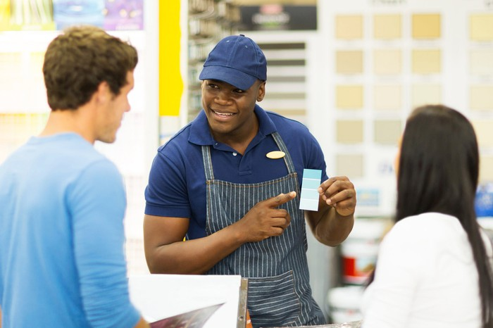 home improvement store employee working with customers on paint color samples