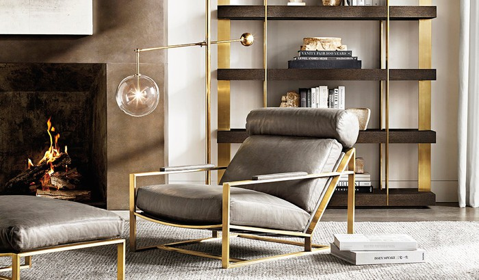 Chair, ottoman, bookshelves, and lamp all in gold and silver coloring, with a gray rug.