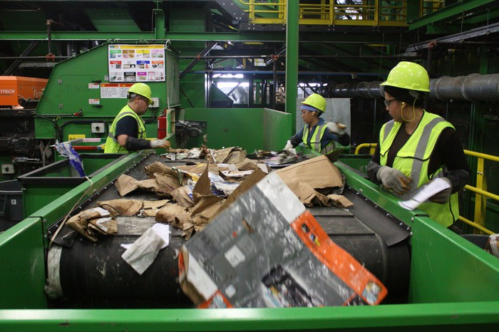 Waste Management workers sort paper at a recycling plant.