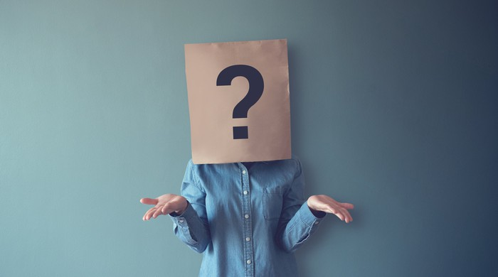 A woman shrugging while a paper bag with a question mark covers her head.