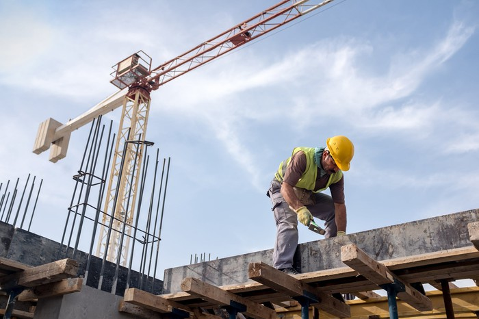 Construction worker handling reinforced concrete with crane in background.