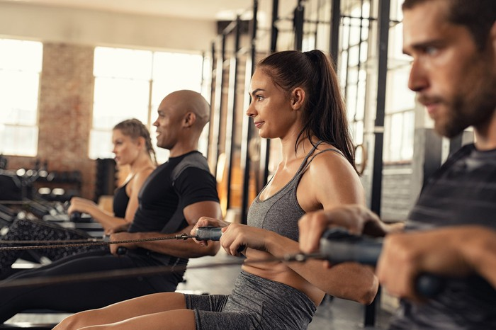 Men and women working out on a rowing machine