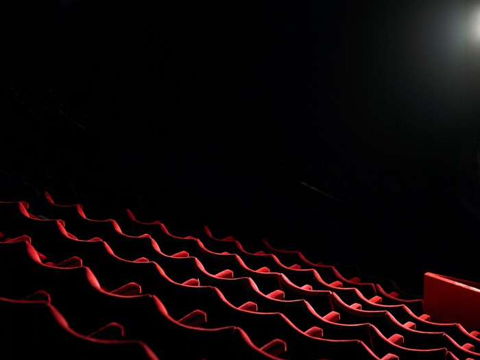 A dark theater with rows of empty seats.