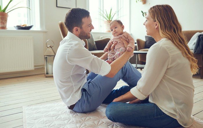 A smiling man sitting on the floor holds a baby on his knee while a smiling woman looks on.
