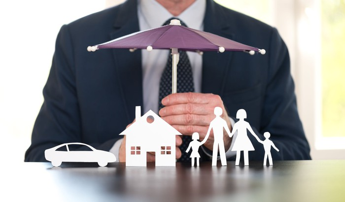 A man in a suit holding an umbrella over tiny models of a family, home, and car made of paper