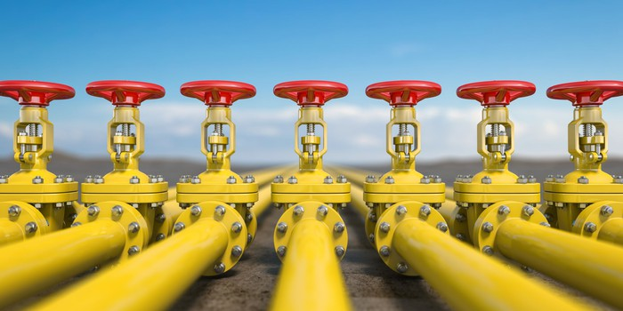 A line  of six yellow oil pipelines with red  handles sticking out on top.