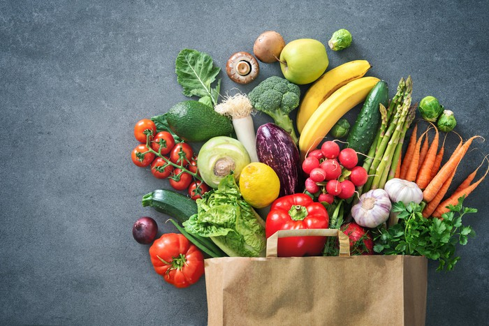 A brown bag full of fresh produce is displayed against a gray background.