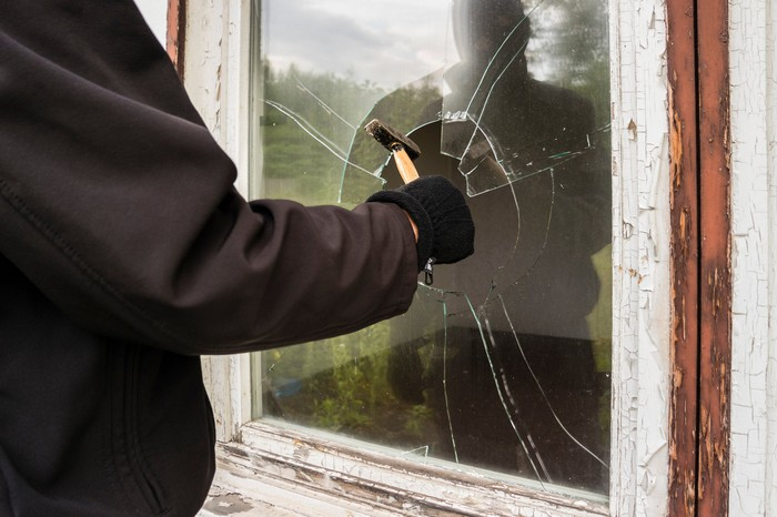 A person in a black jacket breaks a window with a hammer.