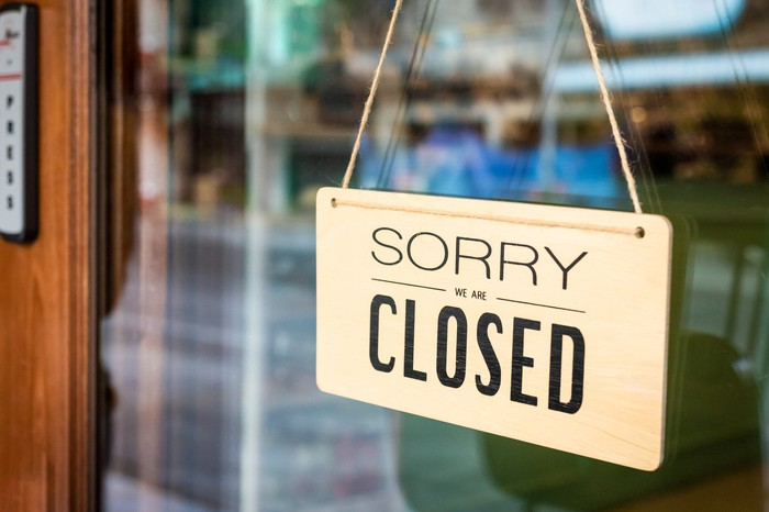 """A sign reading, """"Sorry, we are closed,"""" hangs on a door."""
