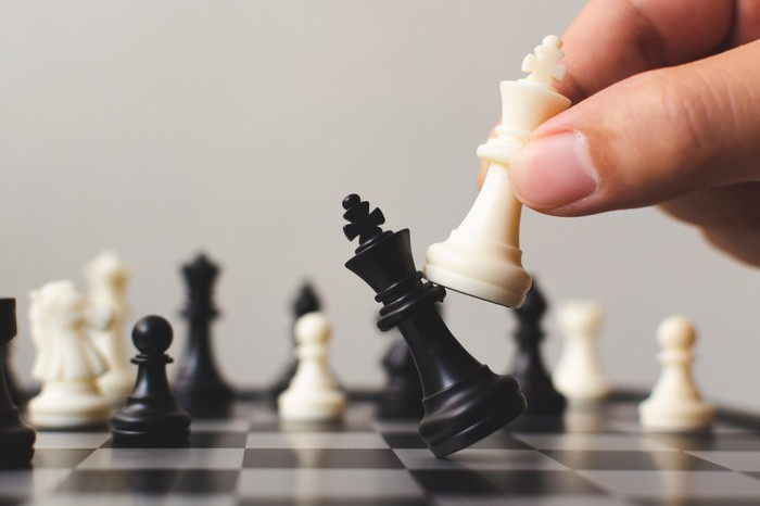 Hand of chess player knocking down a black chess pawn with a white one.