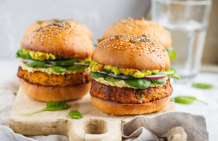 Two plant-based meat burgers sitting on a platter.