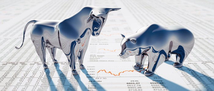 A silver bull standing tall in front of a silver bear, both of which are atop a financial newspaper.