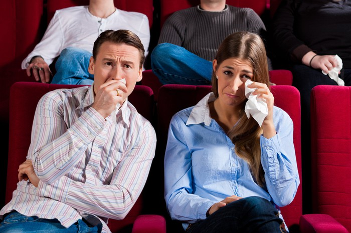 A couple cries in a movie theater.