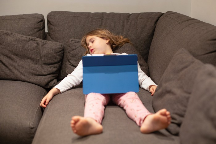 Young girl with computer asleep on a modular couch.