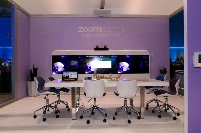 Room with white table and six chairs, purple walls, and big-screen video set-up, with Zoom logo on wall.