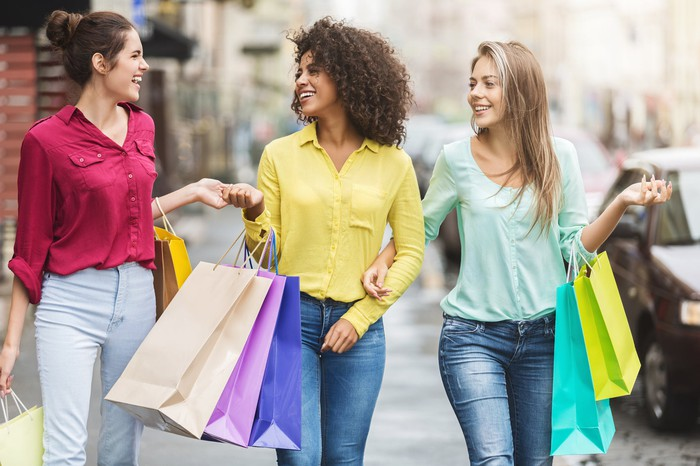 three young women walking down the street with shopping bags