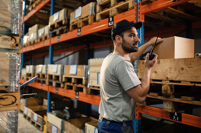 A warehouse worker pulls an item from a shelf.