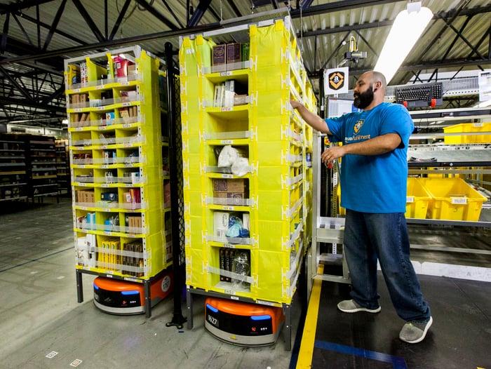 A man grabbing an item off a robot-controlled warehouse shelf.