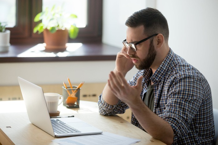 Frustrated man on phone looking at laptop