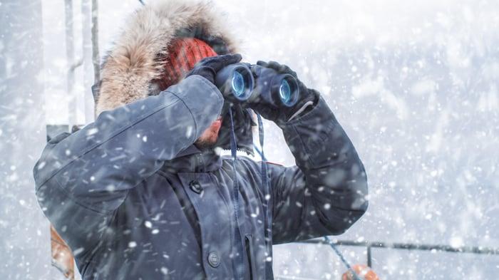 Polar researcher looking through binoculars.
