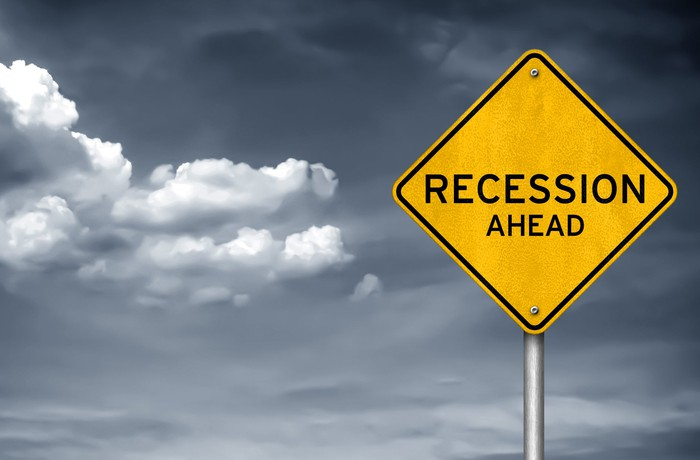 A yellow street sign says recession ahead, with black and white clouds behind it.