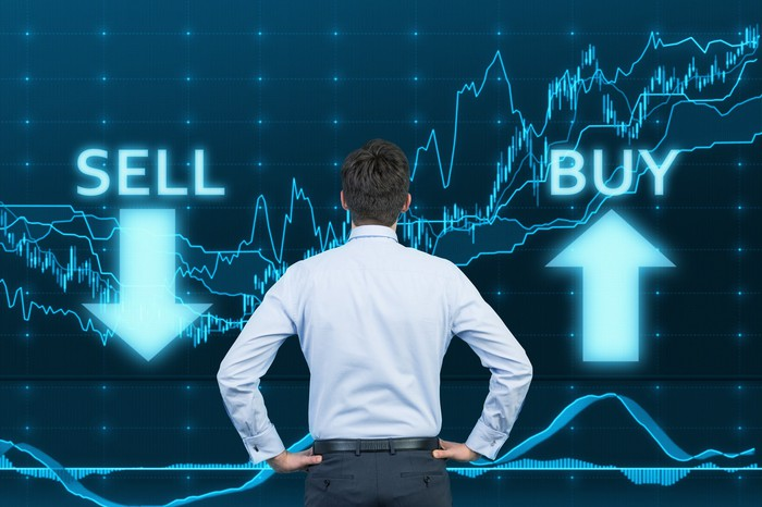 A man with his back to us is looking at a graph and the words sell and buy, with arrows pointing up and down.