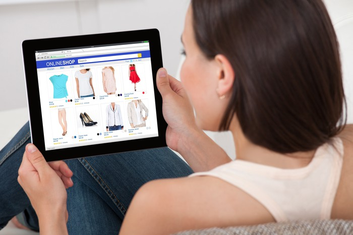 A woman shopping for clothes online using a tablet.