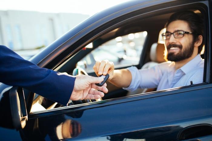 Salesman handing customer keys to a car.