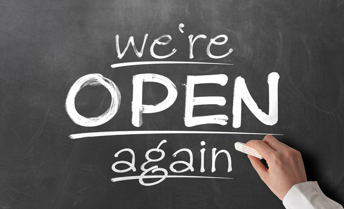 """A chalk board sign that says, """"We're open again."""""""
