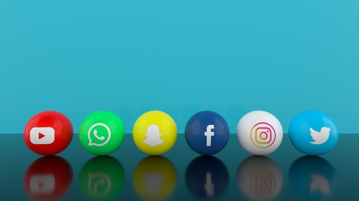 Social media icons balls on a table with a blue background.