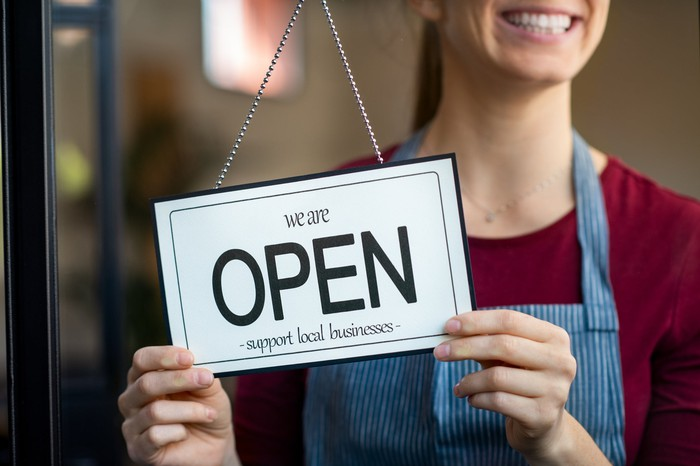Woman holding open sign in storefront window.