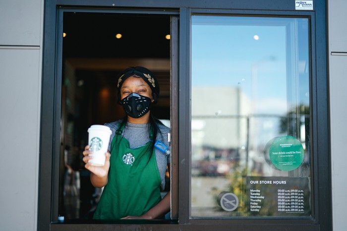 Starbucks barista wearing a mask at the drive-in window.