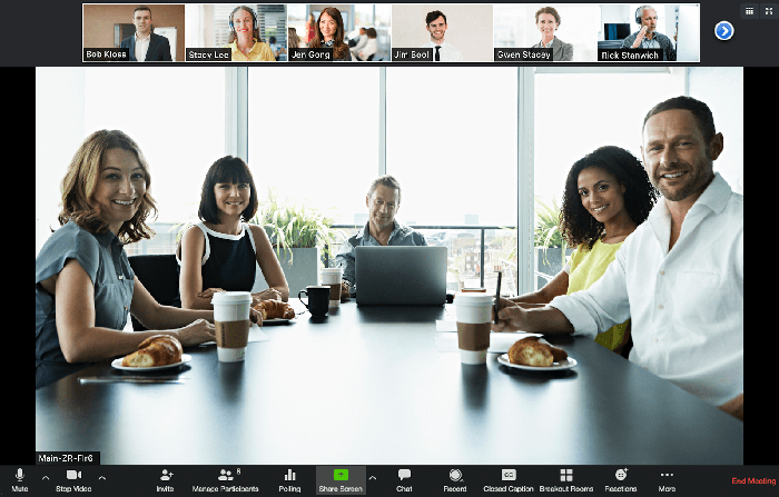 A screen cap from a Zoom video meeting with a group of attendees sitting in a conference room.