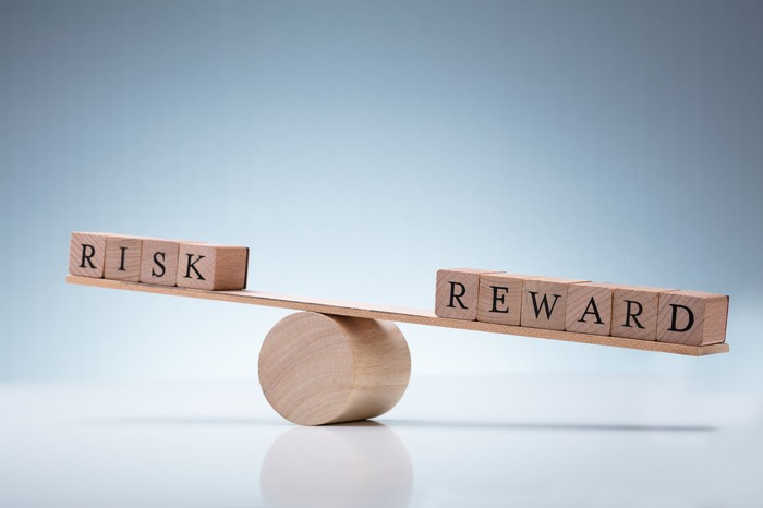 """Wooden blocks spelling out """"risk"""" and """"reward"""" on opposite sides of a seesaw"""
