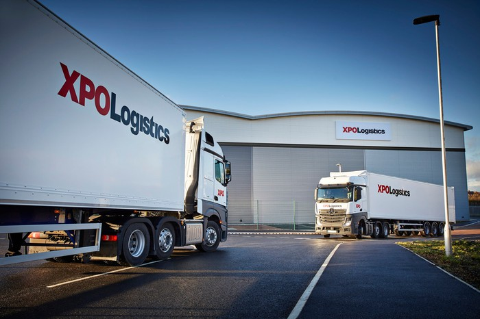 Two XPO semi-trucks at a distribution center.