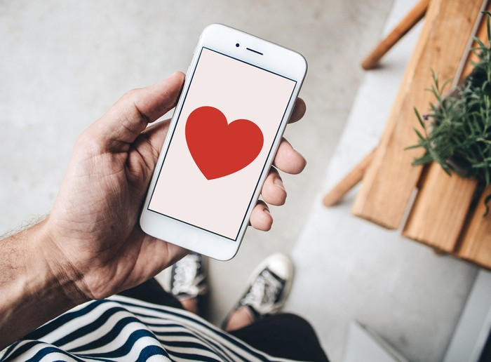 A person holding a mobile phone displaying a heart.