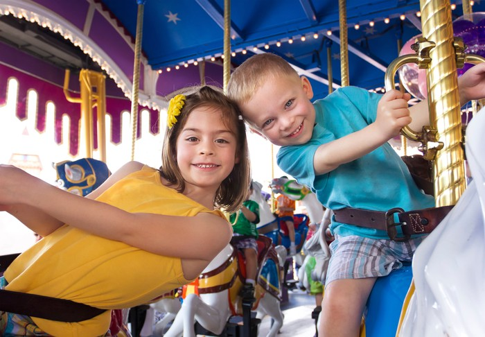 Two children riding a merry-go-round.