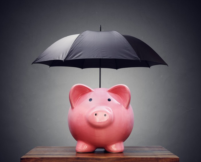 A pink piggy bank protected by a black umbrella above it.