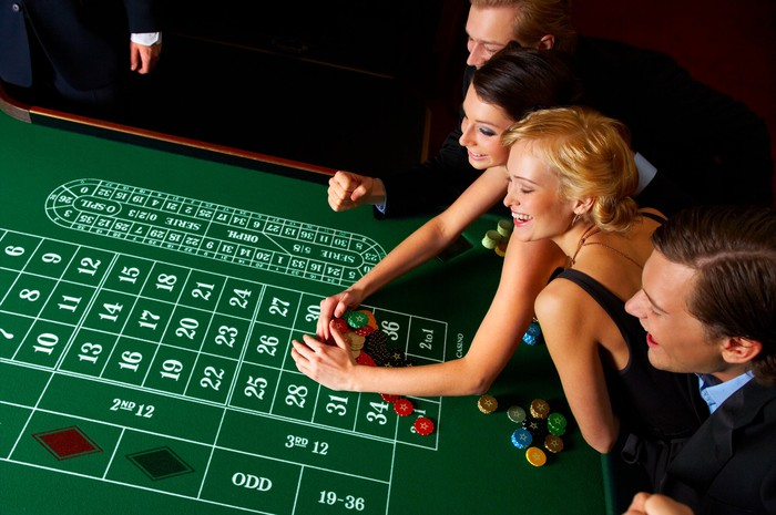 Four well-dressed players at a casino gambling table.