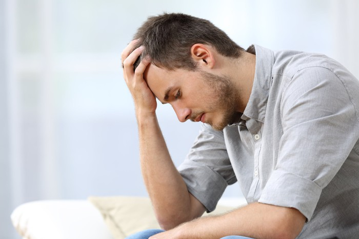 Man with sad expression holds his head in his hand.