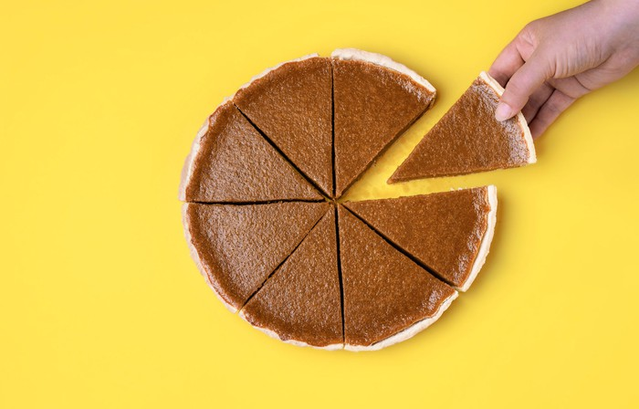 Slice of pumpkin pie being removed from whole pie
