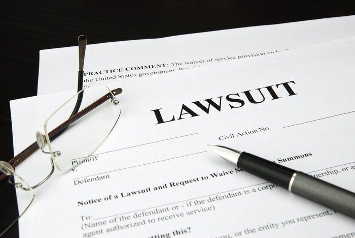 Lawsuit documents lying on a table, with a pen and glasses.