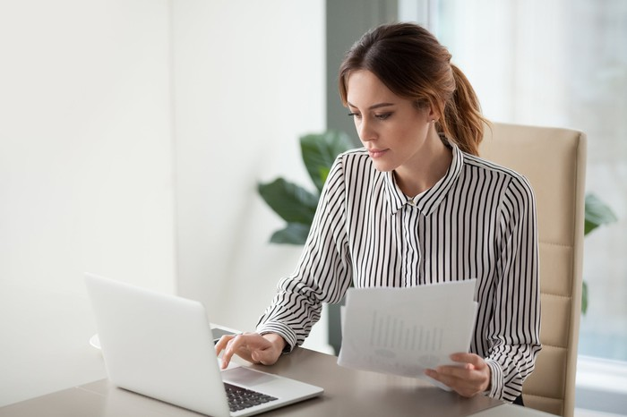 Woman typing on her laptop while holding some papers.