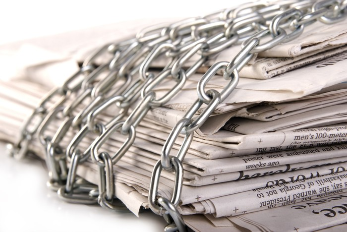 A stack of newspapers with a chain around them.