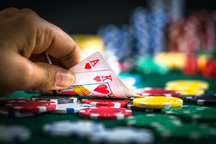 Someone's hand lifting up cards on a poker table filled with chips.