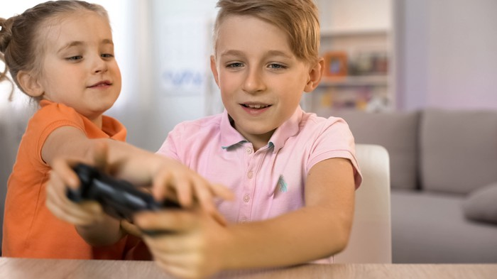 Two children fight over a video game controller.