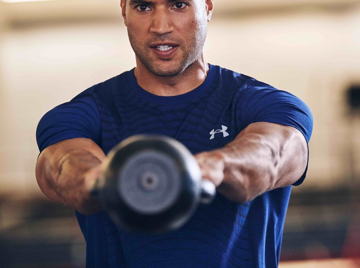 Man in Under Armour shirt exercising with weights
